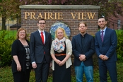 Laura Huinker, assistant professor of business at UIU; Charles Alcaide '15; Sylvia Mork, chief executive officer/administrator at Prairie View Management, Inc.; Nick Reierson '13, Priaire View office assistant; and Jake Baroon '15, pose for a photo at the main gate of Prairie View.