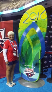 Kathy Guyer stands alongside the giant flip flop that swimmers signed after qualifying for the 2016 Olympics.