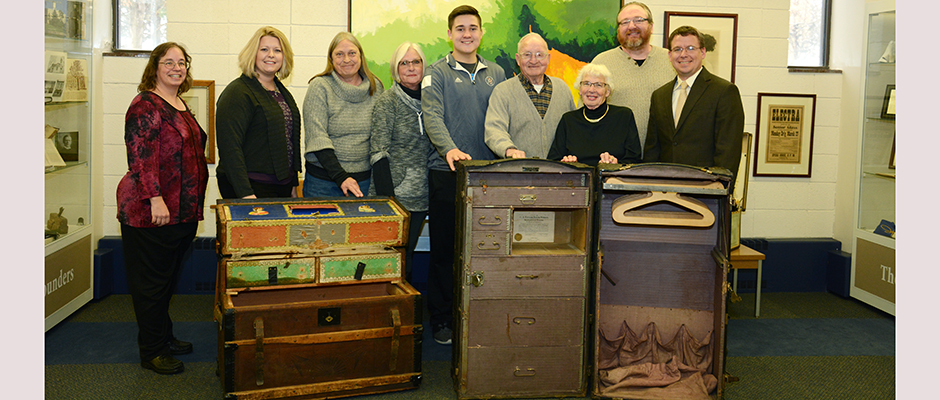 Loyal L. and Norma McLean of Charles City were recently joined by other family members in donating a pair of steamer trunks to Upper Iowa University. The trunks are believed to be nearly 100-years-old and previously owned by UIU alumna and accomplished stage actress, the late Zinita Graf '1913. (From left) Pictured with the trunks at UIU's University Archives are (l-r) UIU Archivist Janette Garcia, UIU Executive Assistant to the President Holly Wolff, the McLean's daughters Cindy (Lockey) and Susan (McGinn), great-grandson Dylan Salinas, Loyal L. and Norma McLean, UIU Director of Library Services Rob Hudson and UIU Vice President for External Affairs Andrew Wenthe.
