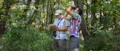 Assistant Professor of Biology Paul Skrade prepares to record data, while senior Chase Grabau attempts to view one of the avian species the two researchers have been studying in northeast Iowa. Skrade and Grabau recently presented their findings at The Wildlife Society's 23rd Annual Conference in Raleigh, North Carolina.